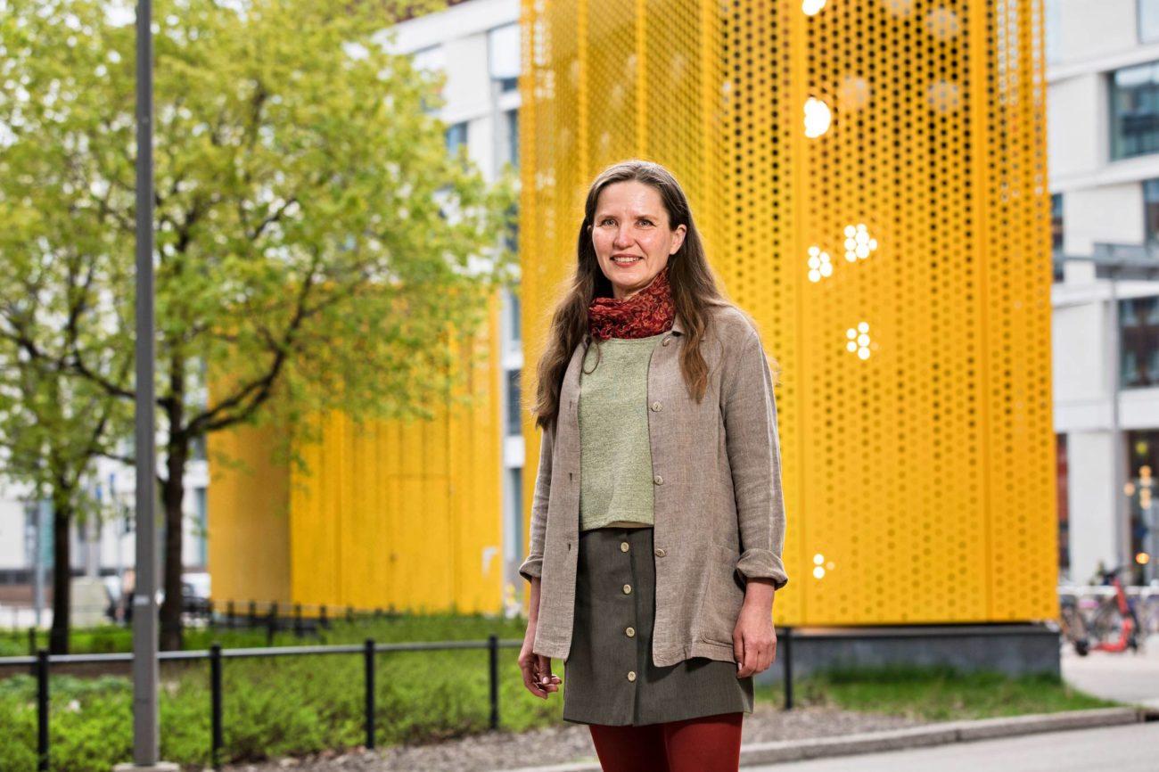 Hanna Sutela seisoo keltaisen talon edessä.