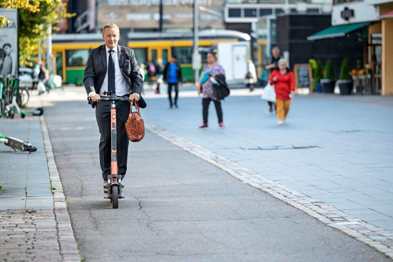 Carl Pettersson ajelemassa sähköpotkulaudalla Helsingin Lasipalatsin edustalla pyörätiellä.