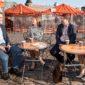 Neljä henkilöä keskustelevat Hakaniemen torilla kahvikojun pöytien ääressä.