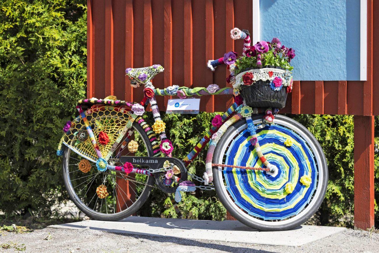 Värikkäillä neulelangoilla koristeltu polkupyörä kesäpäivänä