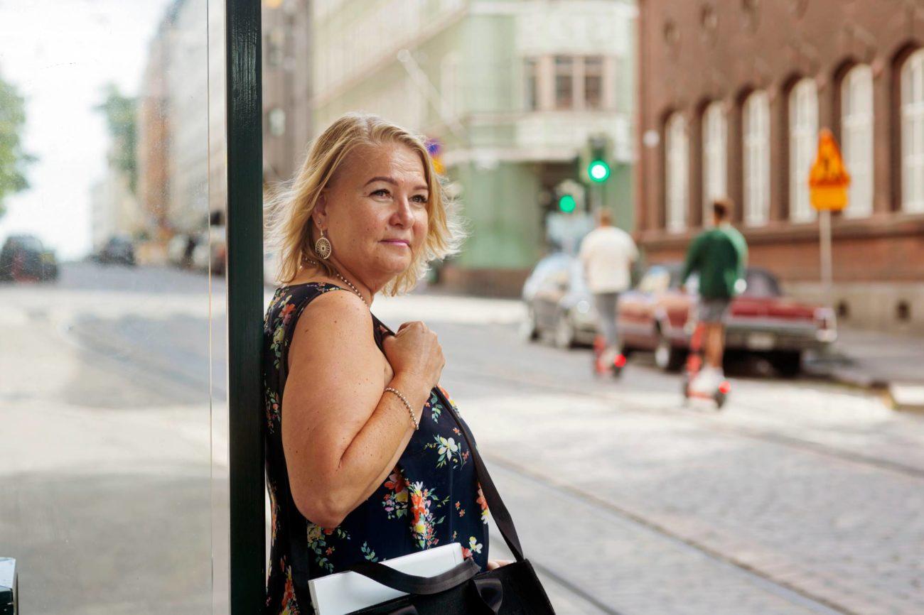 Jaana Saarelainen nojaa raitiotievaunupysäkin kaiteeseen ja katsoo kaupunkikuvaa.